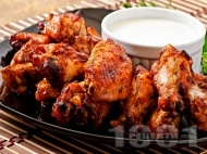 Вкусни печени пилешки крилца глазирани с мед, чесън, кетчуп и сос от нар в алуминиево фолио на фурна